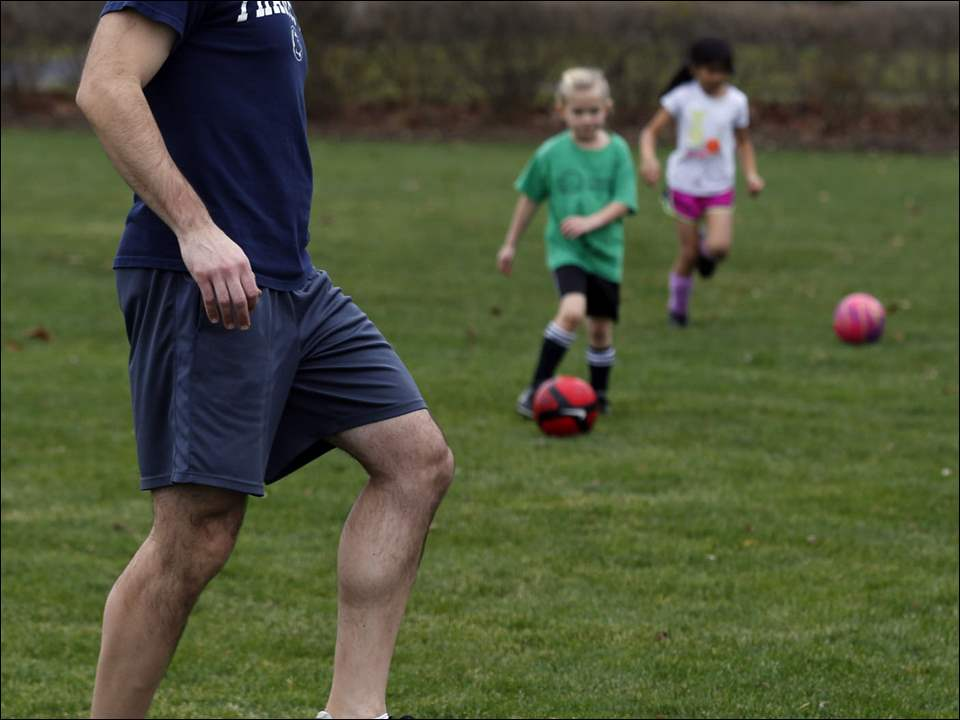 Chris Brown, left, coach of The Ottawa Hills Dynamo Futbol Club Juniors first grade team, demonstrates how to dribble the ball while wearing shorts during practice at Ottawa Hills High School on Sunday.