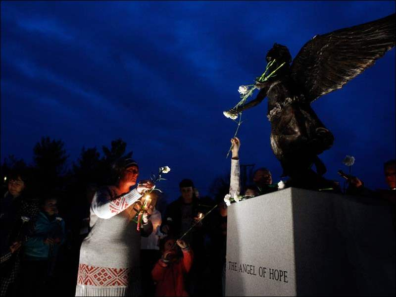 "Heather Honaker goes to place a rose in the arms of the ""Angel of Hope"" during vigil dedicating the new statue at ProMedica Toledo Children's Hospital."