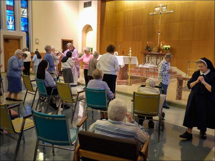 Sisters of Notre Dame take communion for the last time at the Toledo Provincial Center, Tuesday.