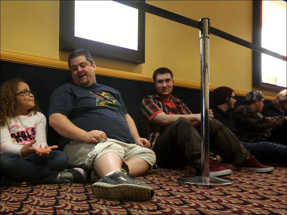 "Kyle Recker, 7, left, talks with her father Chris Liebe, center left, as the pair join other fans in lining up more than three hours early to see ""Star Wars: The Force Awakens"" on Thursday at Rave Cinemas Franklin Park 16 inside the Franklin Park Mall in West Toledo. Mr. Liebe picked Kyle up from school and headed directly to the theater."