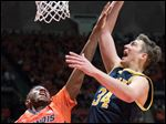 Michigan forward Mark Donnal (34) shoots over Illinois' guard Aaron Jordan (23).