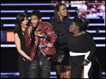 An unidentified guest speaks on stage while Julie Chen, left, Aisha Tyler, and Sheryl Underwood accept the award for favorite daytime TV hosting team for 'The Talk' at the People's Choice Awards.