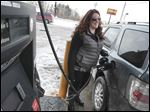 Jennifer Little of Carleton, Mich., pumps gas at the Pilot on Alexis Road, where regular gas was $1.45 a gallon. Last year at this time, Toledo's average price was $1.87 per gallon for regular, while the national average was $2.11.