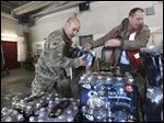 Michigan Nation Guard Sgt. Steve Kiger, left, of Harrison, Mich., stacks cases of drinking water with Red Cross volunteer Franklin Dickerson of Pleasant Ridge Wednesday in Flint, Mich.
