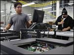 Ardee Maraon, left, and Tony Nuno work on a television in a Newbury Park, Calif., SunBrite factory.