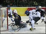 United States goaltender Chanda Gunn makes a save as Finland's Saara Tuominen misses a scoring chance in a 2006 Winter Olympics game in Turin, Italy.
