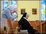 Sister Ethel Mary Camp, left, prays during morning mass at the the Sisters of Notre Dame Toledo Province on April 1.