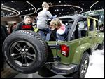 Jack Plumb, 10, left, and Adam Biscan, 12, play in the back of a Jeep Wrangler at the North American International Auto Show in Detroit. Fiat Chrysler is keeping the production of the Wrangler at the Toledo Assembly Complex.