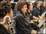 Chyna  McClelland, 15, right, chats with Nasyah Oxner, left,  during rehearsal at Toledo School for the Arts.  Fund-raising has begun to help the youth orchestra become the first to travel to Cuba since relations were restored.