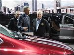 President Obama looks over the Chrysler Pacifica minivan with North American International Auto Show chairman Paul Sabatini, far left, and United Auto Workers President Dennis Williams at the auto show in Detroit.