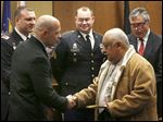 Treatment team member Jordan Garza, left, shakes hands with graduate Army veteran Alfred Cortez during the Veterans Treatment Court graduation ceremony in Toledo Municipal Court.