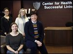At the University of Toledo, Jessie Myler, back left, Haley Dunbar, back right, Mallory Rinckey, front left, and Amy Thompson have been spearheading an effort in Lucas County to raise the minimum age to purchase tobacco products to 21.