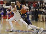 Whitmer's Sam Hickey tries to drive past St. Francis' Jakiel Wells on Friday night. Hickey led all scorers with 25 points.