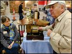 Barney Stickles holds a music box as Ellen Tietjen of Tietjen's Antiques of Lucas, Ohio, looks on at the Maumee Valley Historical Society's 47th annual antique Show in Maumee.  The show was a fund-raiser for the historical society.