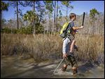 Tyler Pyle, 12, holds a wooden machete as he sits on the shoulders of his father, Shane Pyle, as they search out pythons Jan. 16 in Big Cypress National Preserve, Florida.