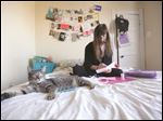 Brittany Adams works on an edition of her fanzine about sex and vulnerability in her bedroom, where she usually works. Her cat Broca commonly keeps her company while she works.