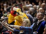 Destiny Coutcher of Millbury doesn't seem fazed as Muddy the Mud Hen dumps popcorn on her while she takes a selfie at the Walleye game Saturday at Huntington Center.