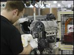 An employee adds the intake manifold to the engine at the Fiat Chrysler plant in Dundee, Mich.
