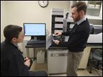 Ryan Carlson, left, and Derek Averill, technical support specialists, explain the operation of the mass spectrometer in the Shimadzu Laboratory for Pharmaceutical Research Excellence at the University of Toledo's Health Science Campus. The lab, opened in 2015, was dedicated Thursday.