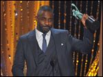 "Idris Elba accepts the award for outstanding male actor in a supporting role for ""Beasts of No Nation"" at the 22nd annual Screen Actors Guild Awards."
