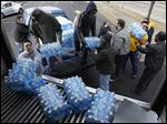 Village Church member Jackie Quinones, bottom left, helps collect bottled water for Flint at the Toledo Police Patrolman's Association parking lot in Toledo in January.