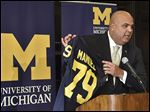 Michigan's new athletic director Warde Manuel holds up a jersey during a news conference on Friday in Ann Arbor.
