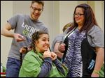 Evan Acri of Bowling Green begins to cut the hair of his girlfriend, Taylor Lody, a senior at BGSU, with some help from volunteers Celina Comes and, behind her, Audra Tolles. Both are from Ambrosia Salon and Spa in Bowling Green.
