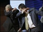 Former coach Lou Holtz, left, and Michigan coach Jim Harbaugh perform a dab during the Signing With the Stars spectacle Wednesday in Ann Arbor. Guests and superstars appeared on stage to welcome the University of Michigan's new recruits on national signing day.