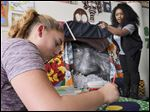 Local artist Merce Culp, right, collaborates with Toledo School for the Arts students for a Black History Month project. Hana Gazwi, 13, paints for the project. Miss Culp urged students to recognize that the history is relevant today.