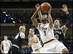 Toledo guard Stuckey Mosley drives to the basket against Western Michigan guard Bryce Moore.