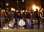Emergency officials gather near the site where two police officers were shot in the Bronx section of New York, Thursday, Feb. 4, 2016. Two police officers were shot while on patrol in a public housing project on Thursday night and suffered non-life-threatening injuries, and a suspect was in custody, authorities said. (AP Photo/Julio Cortez)