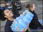 Schi'Ann Crawford, left, and Takela Pickens carry water to be delivered to Flint, Mich., at the YMCA's Youth Opportunity Program center on Bancroft Street. Dozens of Toledo teenagers helped with many traveling to Flint to hand out the water.