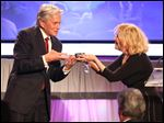 Bette Midler, right, presents Michael Douglas with the Career Achievement Award at the 15th Annual Movies for Grownups Awards.