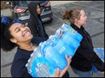 Schi'Ann Crawford, 15, and Takela Pickens load bottled water to be delivered to Flint, Mich., on Friday at the YMCA on East Bancroft Street in Toledo.