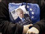 A supporter holds Republican presidential candidate, businessman Donald Trump's book during a campaign rally Monday in Manchester, N.H.