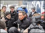 Snow begins to fall as John Kasich talks to reporters after a campaign stop Monday in Plaistow, N.H. The weather could affect turnout for today's presidential primary.