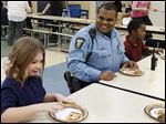Officer Tony Moore eats lunch with fifth grader Bianca Martinez, left, and seventh grader Damar Smith during a new 'Blue Lunch Special' outreach program at Rosa Parks Elementary. Officers also visited five other city schools Wednesday.