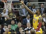 LeBron James drives to the basket against Los Angeles Lakers' Kobe Bryant in the first half.