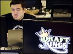 Len Don Diego, a manager at DraftKings daily fantasy sports, works at its offices in Boston. Roughly 19 states are considering bills to regulate the industry, in which players compete online for prizes by picking teams of athletes.