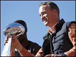 Denver Broncos quarterback Peyton Manning holds the Lombardi Trophy during a parade for the NFL football Super Bowl champions, Tuesday, in Denver.