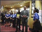 Romules Durant, superintendent of Toledo Public Schools, is presented with books by Anthony Stewart-King II, 13, holding book, left, and Nia Thomas, 12,  right,at the Jones Leadership Academy.  The presentation, made with other members of the school's chess club, in background, was made as part of a Black History Month celebration.