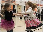 Renea Edmondson, left, and Jordyn Thompson enjoy dancing after the marriage of Q and U in their school gym. The event is to help students remember that the letters Q and U almost always work together and that very few words contain a Q without an accompanying U.