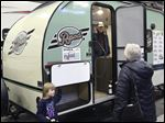 Tom and Beverly Olah of Rossford shop for an RV with their granddaughter Erica, 3, during the annual Camp and Travel Regional RV Show at SeaGate Centre in downtown Toledo.