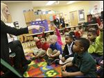 JaCarri Braswell, 5, right, raises his hand to answer a question posed to the class of Glenwood kindergartners.