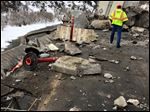 A highway worker examines debris from a rock slide on I-70 in Glenwood Canyon in western Colorado on Tuesda. The rocks damaged the tractor-trailer rig visible in the background, but state officials said no one was injured. The interstate was closed in both directions while the canyon walls were inspected and the damage was repaired.