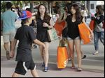 Tourists from Taiwan carry shopping bags as they walk along Lincoln Road Mall, a pedestrian area featuring retail shops and restaurants in Miami Beach, Fla.