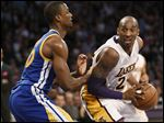 Kobe Bryant of the Lakeers handles the ball while Golden State's Harrison Barnes defends.