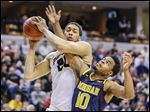 Purdue's A.J. Hammons, left, who scored 27 points, gets tied up with Michigan's Derrick Walton, Jr.  Walton scored 14 for the Wolverines.