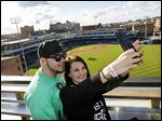 Sari Rahman and Kayla Hopson take a picture from the roof during a St. Patrick's Day party in the Fleetwood Building in Hensville, a downtown entertainment district. The official grand opening of Hensville will be the Hens' April 7 opener.
