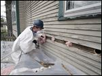 Robert Huber of Neighborhood Housing Services blows insulation into a home on Erie Street on Wednesday in Toledo.  Lucas County officials held a news conference at the home to promote 'Living Green, Saving Green,' a program to provide energy audits to homeowners.
